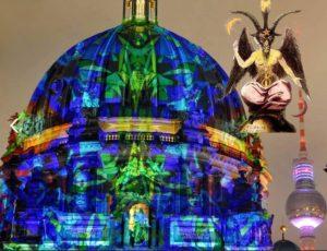 Il Duomo di Berlino, Cattedrale della Chiesa Evangelica Luterana, illuminato durante il Festival of Lights 2016 a confronto con una riproduzione del Bafometto.